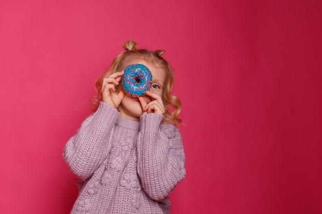 Fröhliches kleines mädchen mit einem donut. das kind gönnt sich essen. spaß mit donuts