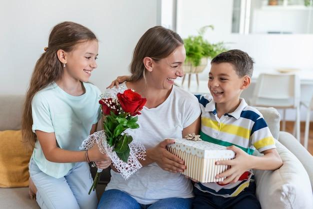 Fröhliches kleines mädchen mit geschenkbox und jüngster bruder mit rosenstrauß lächelt und gratuliert glücklicher mutter am muttertag zu hause. schönen muttertag!
