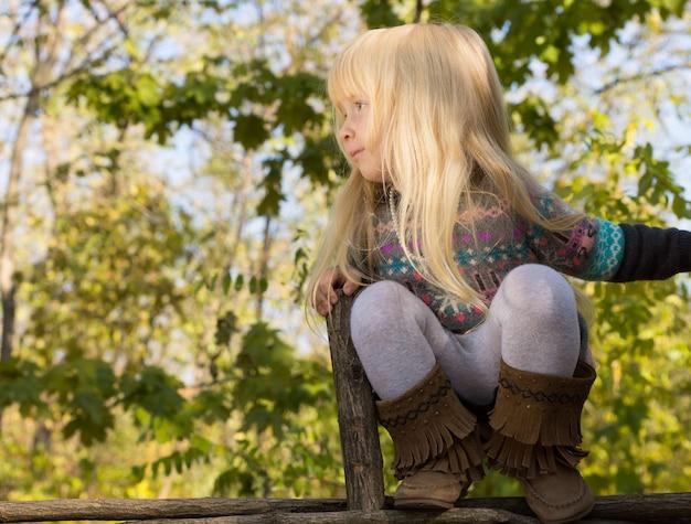 Fröhliches kleines mädchen mit langen blonden haaren, das auf einem holzzaun draußen im garten balanciert und mit einem lächeln links vom rahmen schaut, exemplar copy