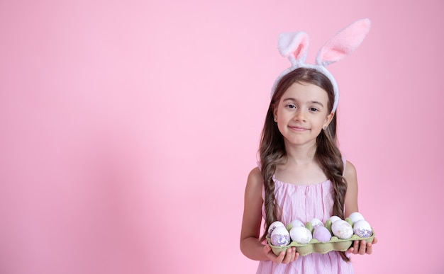 Fröhliches kleines mädchen mit osterhasenohren und einem tablett mit eiern in ihren händen auf einer rosa wand. osterferienkonzept.