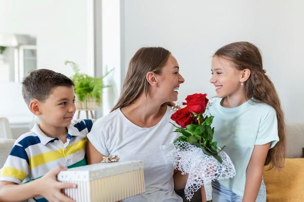 Fröhliches kleines mädchen mit rosenstrauß und jüngster bruder mit geschenkbox, die glückliche mutter am muttertag zu hause lächelt und gratuliert. schönen muttertag!