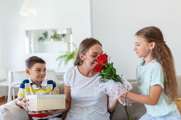 Fröhliches kleines mädchen mit rosenstrauß und jüngster bruder mit geschenkbox lächelnd und glückliche mutter am muttertag zu hause gratulieren. schönen muttertag!