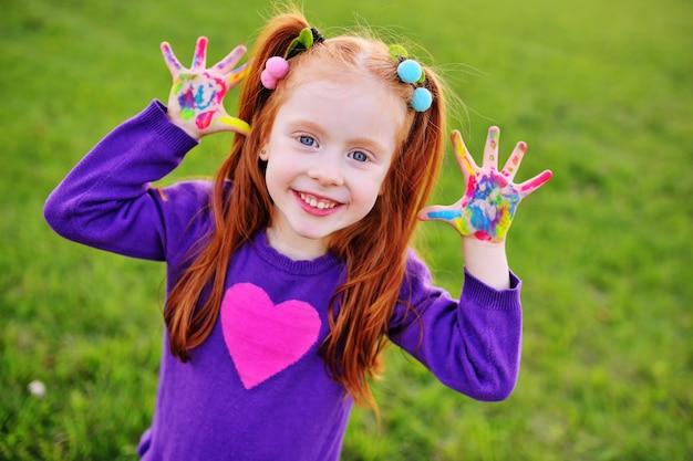 Fröhliches kleines mädchen mit roten haaren zeigt ihre hände schmutzig mit bunten farben und lächelt