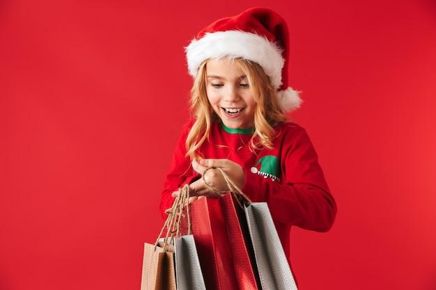 Fröhliches kleines mädchen mit weihnachtsmütze, das isoliert steht und einkaufstaschen trägt