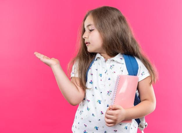 Fröhliches kleines schönes mädchen mit langen haaren mit rucksack, das ein notizbuch hält und etwas mit dem arm ihrer hand präsentiert, das auf rosa steht