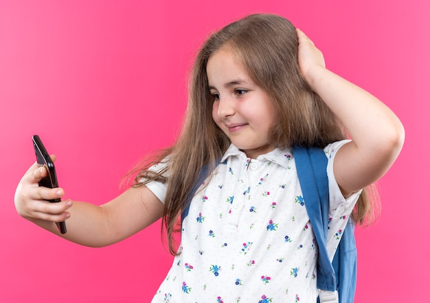 Fröhliches kleines schönes mädchen mit langen haaren mit rucksack macht selfie mit smartphone und lächelt selbstbewusst auf rosa