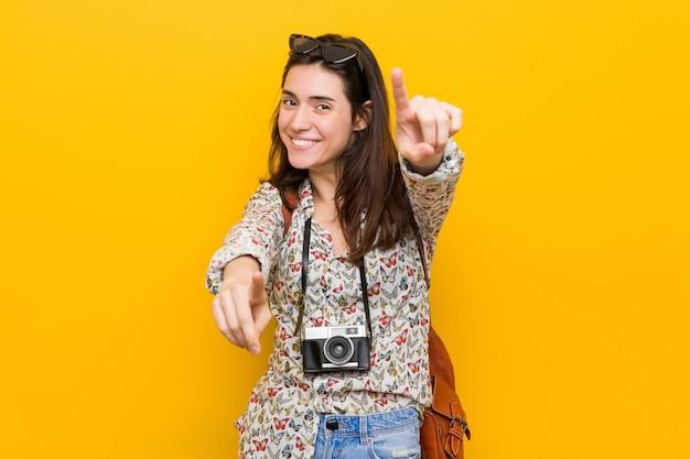 Fröhliches lächeln der jungen brünetten reisendenfrau, die nach vorne zeigt.
