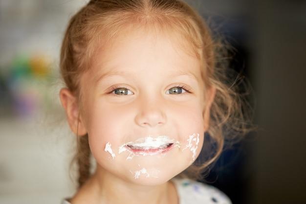 Fröhliches lächelndes kindermädchen, das einen köstlichen kuchen isst und daumen hoch zeigt. mund in sahne. fröhliche sorglose kindheit