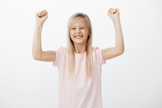 Fröhliches lächelndes kleines mädchen hebt die hände, gewinnt und triumphiert