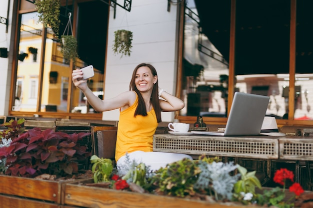 Fröhliches lächelndes mädchen im straßencafé im freien, das am tisch mit laptop-pc-computer sitzt und in der freizeit selfie-aufnahmen auf dem handy im restaurant macht