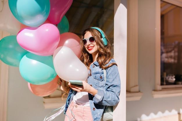 Fröhliches lächelndes mädchen in der stilvollen sonnenbrille, die zum ereignis geht und lieblingsmusik in den kopfhörern hört. entzückende junge frau, die retro-jeansjacke trägt, die bunte luftballons zur geburtstagsfeier trägt.