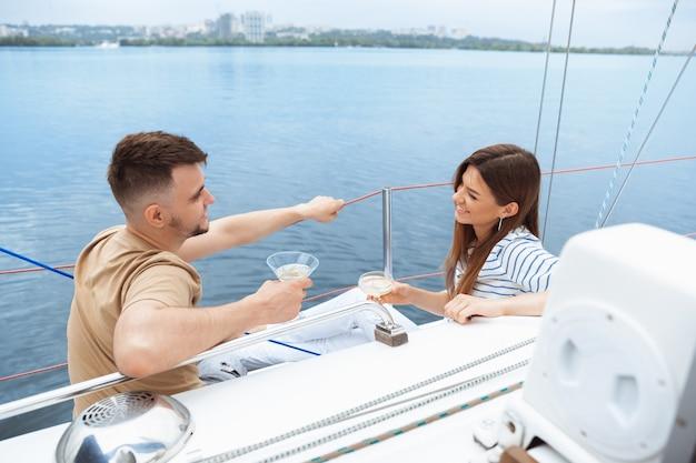 Fröhliches lächelndes paar, das wodka-cocktails auf der bootsparty im freien trinkt, fröhlich und glücklich.