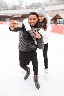 Fröhliches liebespaar, das auf eisbahn im freien schlittschuh läuft, macht selfie