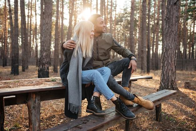 Fröhliches liebespaar, das draußen im wald sitzt