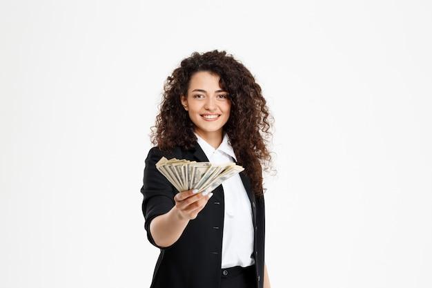 Fröhliches lockiges geschäftsmädchen, das geld hält