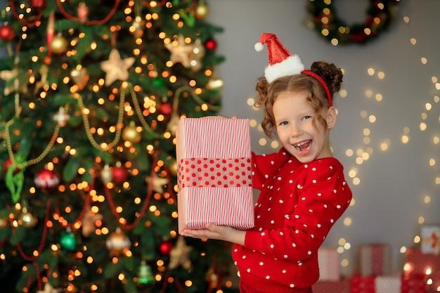 Fröhliches lustiges kleines mädchenbaby mit neujahrsgeschenken durch den baum