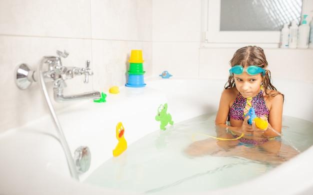 Fröhliches lustiges mädchen in blauen wassergläsern spielt mit einer wasserpistole, während in einem badezimmer mit wasser und hellen spielzeugen sitzend