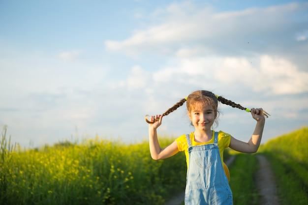 Fröhliches mädchen auf einem gelben sommerfeld lächelt und hält sich an den zöpfen. freude, sonniges wetter, urlaub.abwehr gegen mücken und insekten. lifestyle, freundliches gesicht, portrait, freiheit genießen