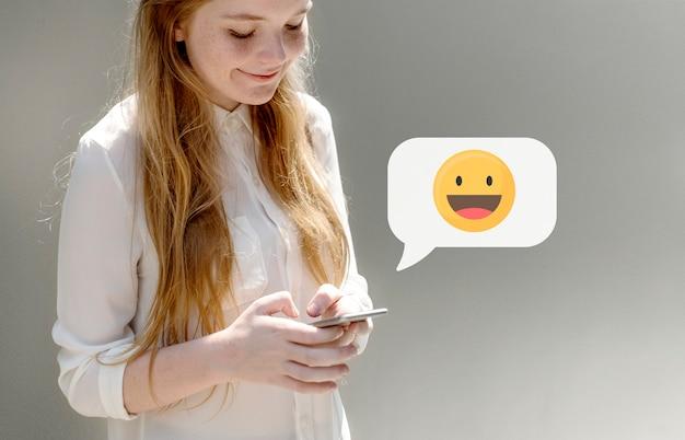 Fröhliches mädchen, das auf ihrem telefon eine sms sendet