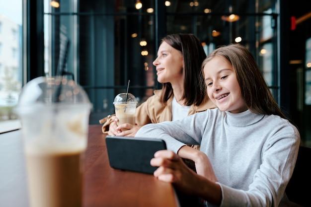 Fröhliches mädchen, das lustiges video im smartphone beim sitzen im café mit ihrer mutter auf hintergrund schaut, der durch fenster schaut