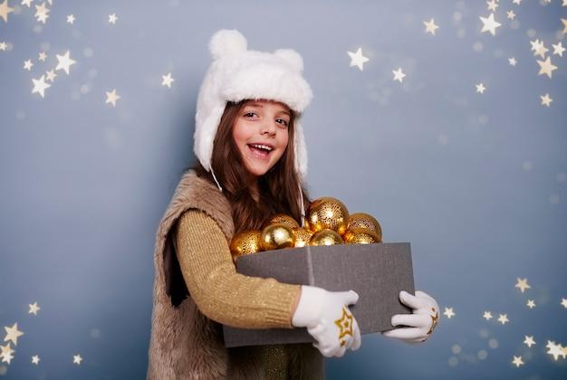 Fröhliches mädchen, das schachtel mit weihnachtskugeln hält