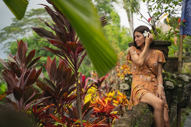 Fröhliches mädchen, das sich eine blume ins haar steckt, während es vor der kamera posiert und tropische fotos für ihren blog macht