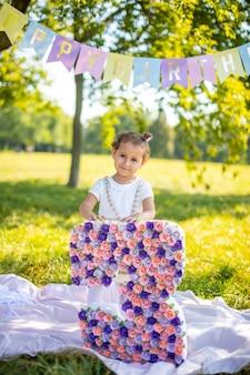 Fröhliches mädchen, das spaß am kindergeburtstag auf einer decke mit papierdekorationen im park hat