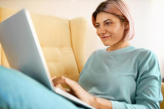 Fröhliches mädchen, das videospiele online über laptop spielt.