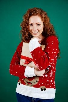Fröhliches mädchen, das weihnachtsgeschenk umarmt