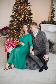 Fröhliches mädchen, das weihnachtsgeschenke von den eltern bekommt