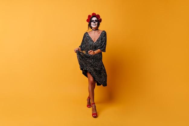 Fröhliches mädchen geht leicht und hält saum ihres kleides. brünette mit make-up auf karnevalslächeln.