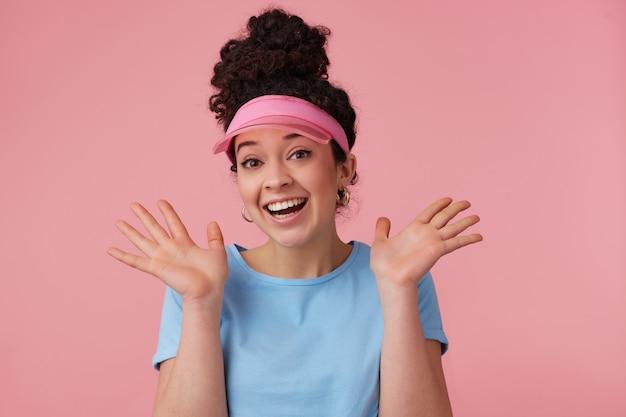 Fröhliches mädchen, glückliche frau mit dunklem lockigem haar brötchen. trägt rosa visier, ohrringe und blaues t-shirt. hat sich geschminkt. menschen- und emotionskonzept