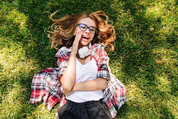 Fröhliches mädchen im lässigen outfit, das im park aufwirft. überkopfaufnahme der lachenden fröhlichen dame, die auf gras liegt.