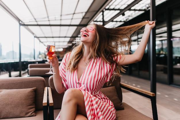 Fröhliches mädchen im stilvollen gestreiften kleid, das spaß im café hat und cocktail trinkt. lachende blonde kaukasische frau, die mit ihren haaren spielt, während sie im restaurant aufwirft.