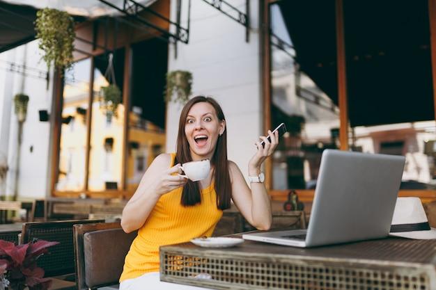 Fröhliches mädchen im straßencafé-café im freien, das am tisch mit laptop-pc sitzt, sms auf dem handy sendet, in der freizeit eine tasse tee im restaurant trinkt