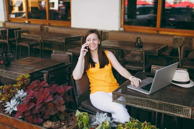 Fröhliches mädchen im straßencafé im freien, das mit laptop-pc am tisch sitzt, mit dem handy spricht, angenehme gespräche führt, im restaurant in der freizeit