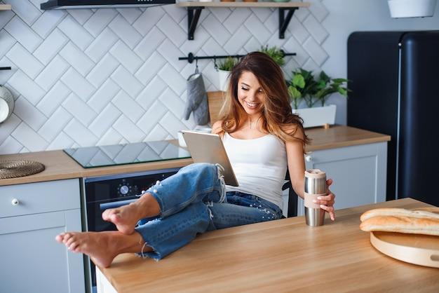 Fröhliches mädchen im weißen t-shirt mit tablet-computer beim entspannen in einem stuhl zu hause in der gemütlichen küche.