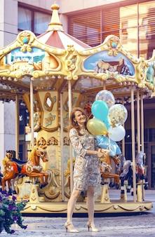 Fröhliches mädchen in den toskanischen wiesen mit bunten luftballons, gegen den blauen himmel und die grüne wiese. toskana, italien