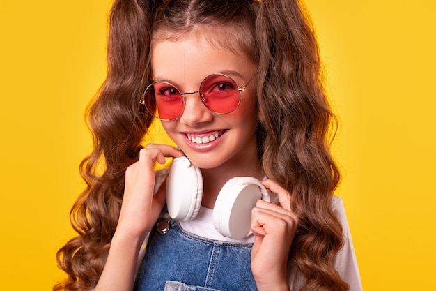 Fröhliches mädchen in der trendigen sonnenbrille, die drahtlose kopfhörer am hals berührt und mit lächeln schaut