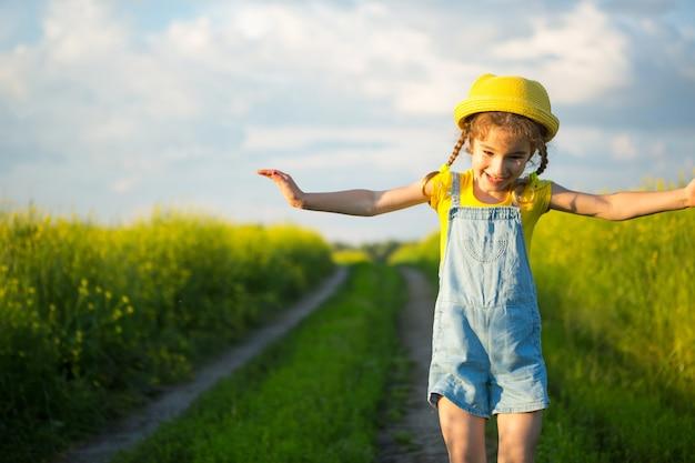 Fröhliches mädchen in einem gelben hut auf einem sommergebiet lacht und lächelt. freude, sonniges wetter, urlaub.abwehr gegen mücken und insekten. lifestyle, freundliches gesicht, nahaufnahme, freiheit genießen