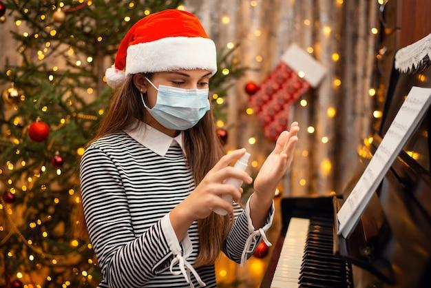 Fröhliches mädchen in roter weihnachtsmütze und schützender medizinischer maske, die händedesinfektionsmittel auf hände anwendet