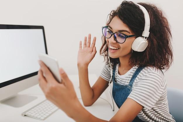 Fröhliches mädchen in stilvollem hemd und kopfhörern kommuniziert mit freund per videolink