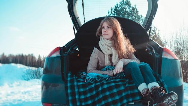 Fröhliches mädchen in strickkleidung, schal und plaid, das auf einem lkw des autos im winterwald sitzt - reisen mit dem auto