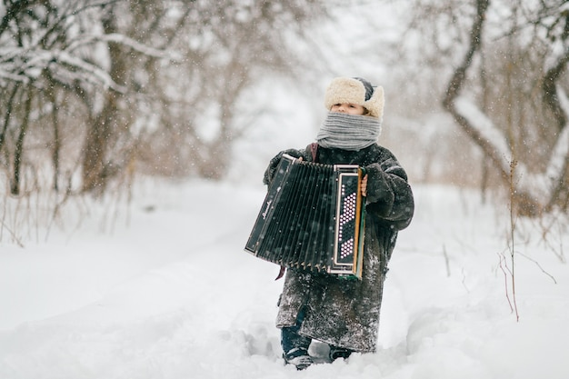 Fröhliches mädchen in übergroßer warmer gepolsterter jacke, die am wintertag mit akkordeon auf verschneiter straße steht
