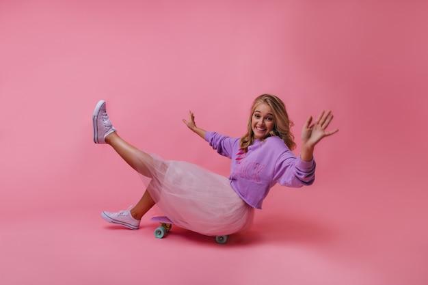 Fröhliches mädchen in weißen gummischuhen, die auf skateboard sitzen. lachende aufgeregte dame, die herumalbert.