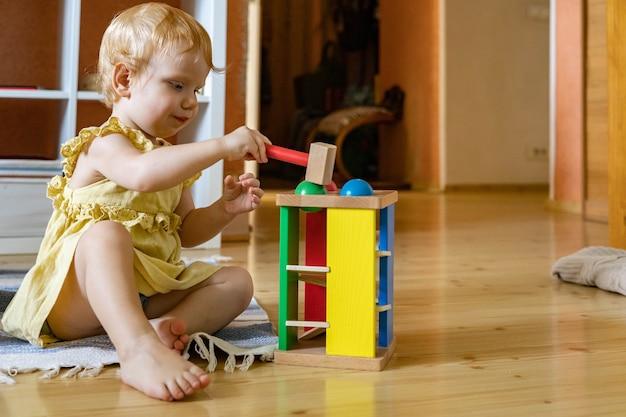 Fröhliches mädchen kleinkind schlägt holzhammer auf farbige bälle frühe entwicklung ökologisches spielzeug