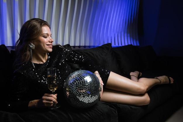 Fröhliches mädchen mit discokugel und champagnerflöte, die auf weicher bequemer couch im nachtclub beim genießen der party liegt