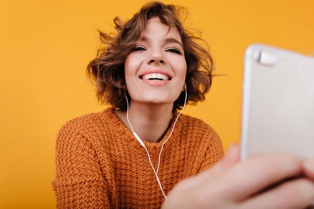Fröhliches mädchen mit gewellter frisur, die musik in den kopfhörern hört