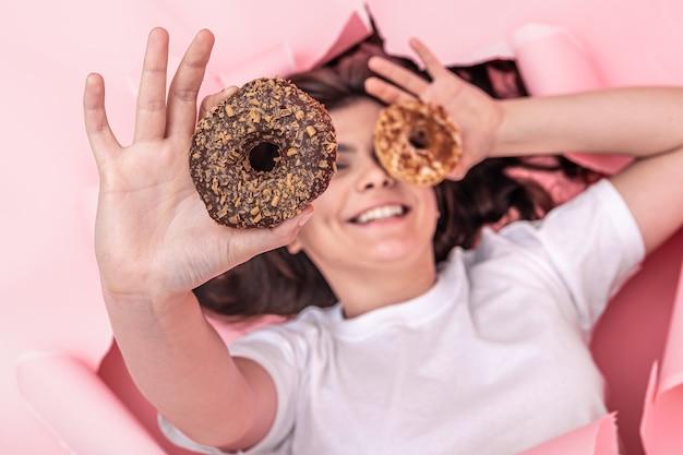 Fröhliches mädchen mit hellen donuts auf einem rosa papierhintergrund