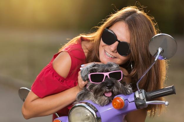 Fröhliches mädchen mit hund in der sonnenbrille, auf einem lila moped, konzept